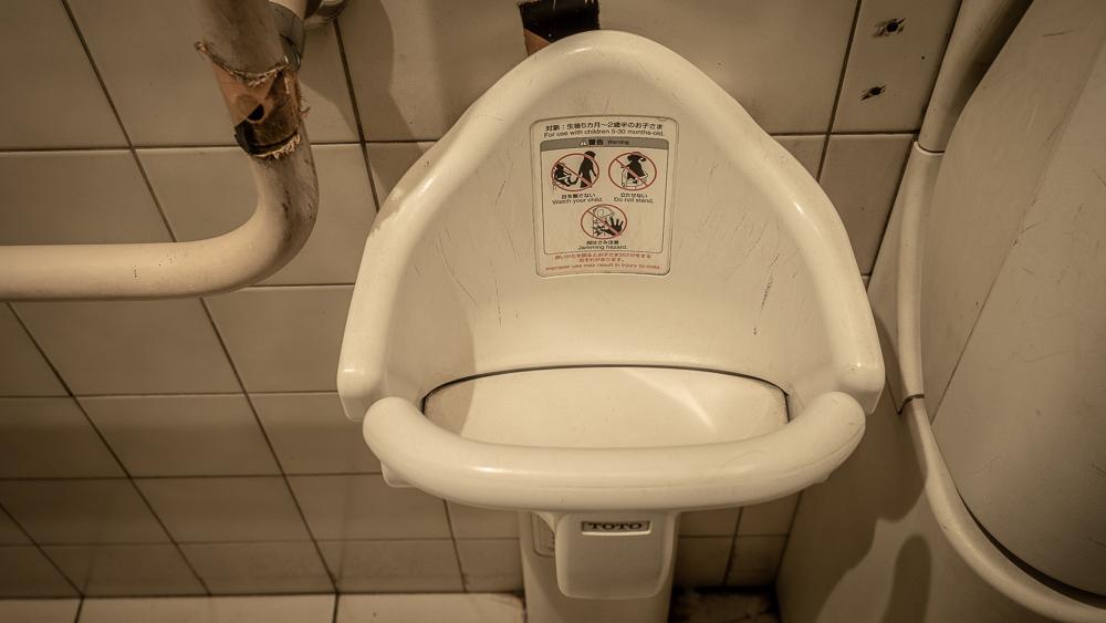 Dzieci mogą usiąść w składanym siedzonku wiszącym na ścianie japońskiej toalety